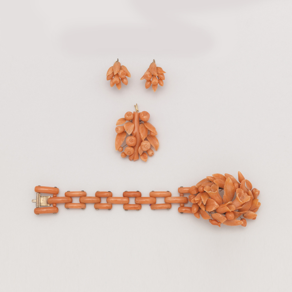 Links of pink coral joined with gold rivets; ornamental clasp elaborately decorated with leaves, flowers and fruit carved in coral and mounted on gold stems.