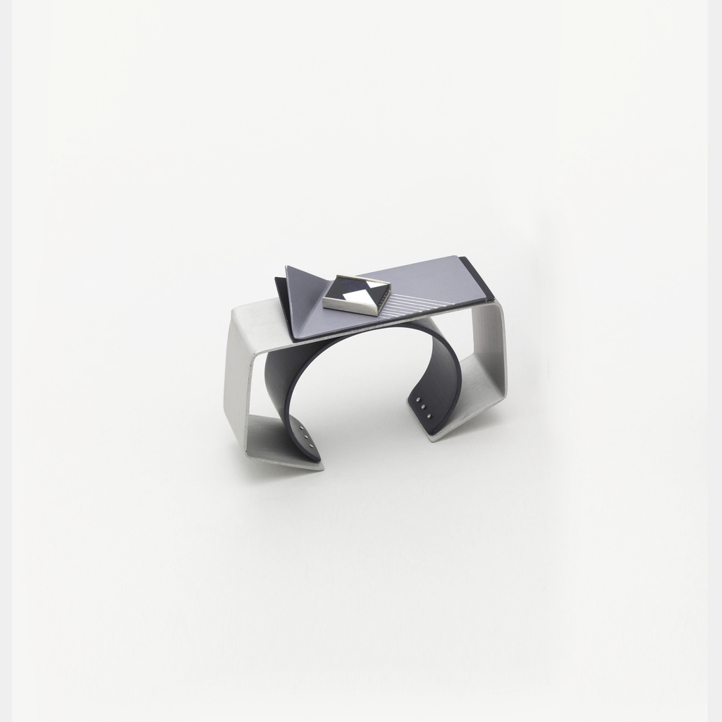 An outer rectangular frame in steel-colored aluminum, surrounding a black cuff of anodyzed aluminum, the top of the bracelet with two rectangles of anodyzed aluminum with upbent corners, with a rectangular box of black and white onyx chequerboard