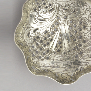 Pierced and shaped circular bowl, in diaper pattern. Bowl engraved with a sailing ship near a river bank surrounded by foliate scrolls. Stem with coin topped by twisted section below a windmill terminal with revolving wings.