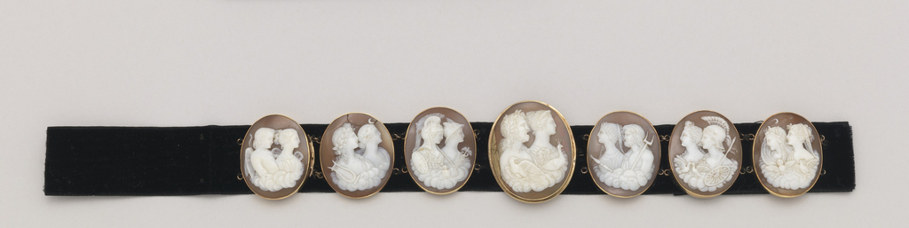 One oval cameo (a) set as brooch. Six smaller oval cameos (b-g) with small connecting chains (one has slot for clasp). All seven with design of pairs of gods and goddesses with attributes; all mounted in gold. Ovals are sewn to a black velvet ribbon, brooch in center, flanked by three ovals from bracelet on either side.