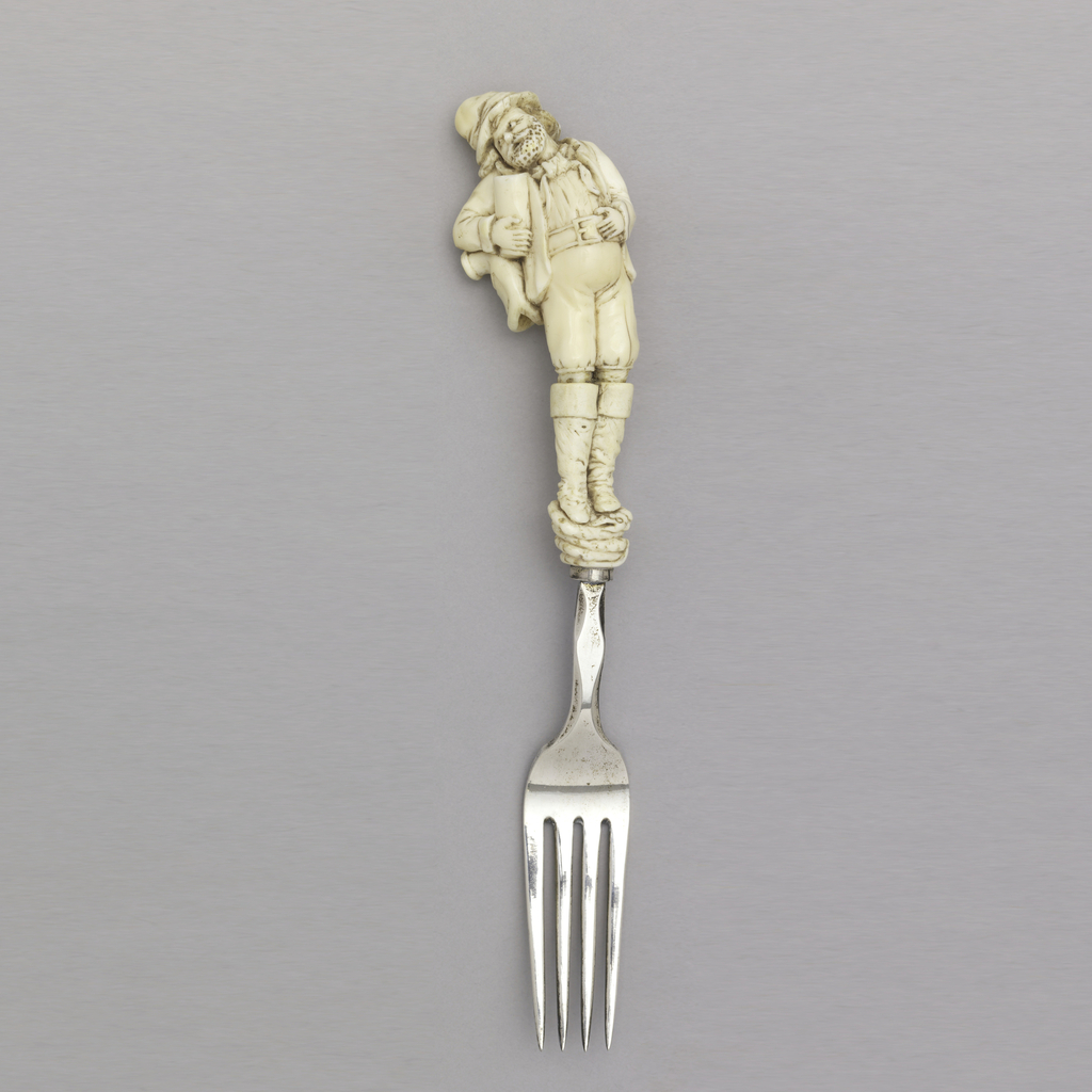 Four tine fork with faceted shank. Handle formed as a fully modelled, carved ivory bearded man leaning to his right, clutching a drinking cup close to his side with his right hand and his belly with his left hand, a flask hung over his shoulder. He stands on a coiled serpent.