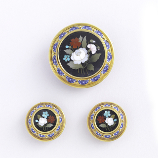 """Florentine Mosaic"" parure, set in gilt metal filigree and granule decoration surrounding circles (upper portion of earrings), and half-circles of porcelain or enamel. The parure is composed of: brooch; pendant locket; pair of cuff studs; pair of earrings. A specially designed box (-3 G) of black ""morocco"" lined with pale blue satin."