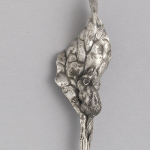 Handle in the form of a patinated ant carrying a larva along a toothed leaf.
