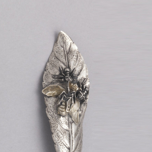 Handle in the form of a two patinated ants surrounding a gilded dead fly.