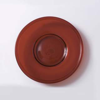 Red circular dish with flat border and rolled rim.