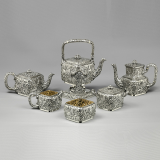 Tea set in silver with a repeating design of repousse leaves and berries, against a chased background of overlapping leaves.