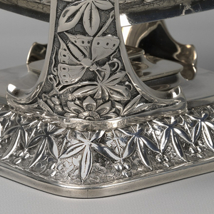 The stand is square; a curved stepped edge is ornamented with a repeating design of repousse leaves and berries, against a chased background of overlapping leaves.  From opposite corners rise the support brackets for the kettle, formed of tapered curved bands with a trefoil top.  The supports are decorated with repousse designs of vines, leaves, and butterflies, arranged asymmetrically.  The square body of the teapot is similarly decorated.  A flush-hinged flat lid, a foliate knop, a curved spout with foliate terminal, and a square handle fitted with ivory insulators, are all similarly decorated.  The stand is fitted with a plain, square spirit lamp with removable wick holder/cover.
