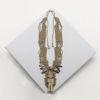 Carved bone figure of man/god backed by woven panel, suspended from flat woven and beaded collar in tan and rosey tones.