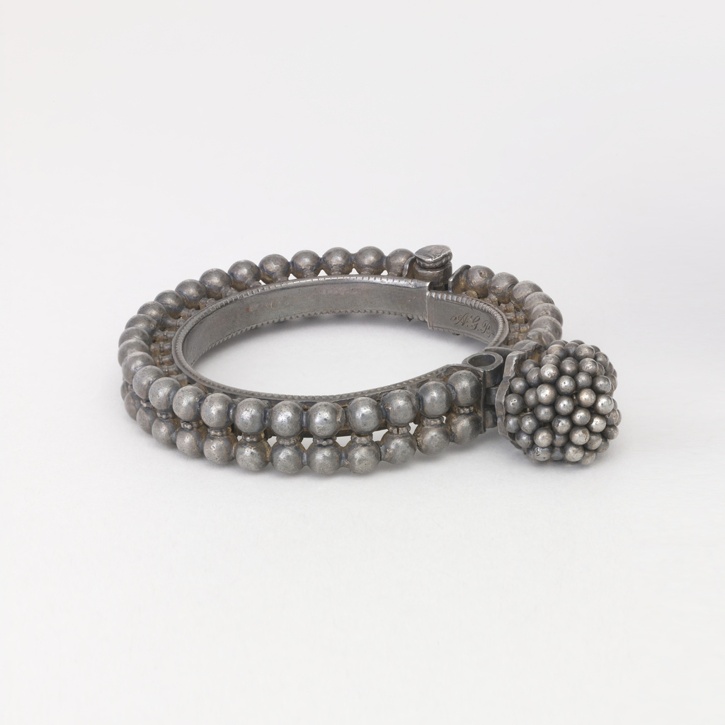 "Hinged braclet with pin fastening. Bracelet is ornamented with a double row of balls set on short stems, smaller balls cover the clasp. Initials on inside: ""A G R - M C M"""