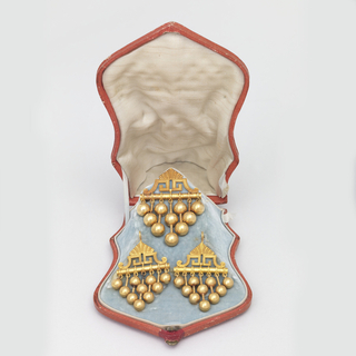 (A)Brooch with a bar surmounted by pointed ornament of Greek Key and leaf design, below the bar are 7 pendant balls and rods in four lengths.  (B)The box is designed to hold the set (with earrings 1946-50-38 a,b) covered in red leather, lined with blue velvet and white satin.