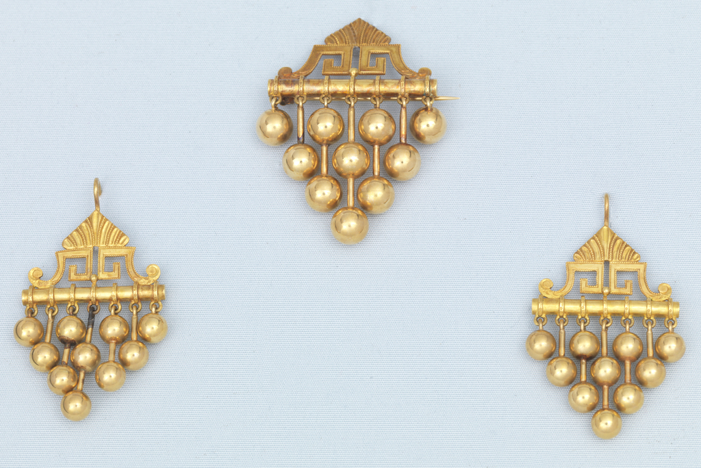 a) Earrings in design of bar surmounted by pointed ornament of Greek key and leaf; below bar are seven pendants (balls and rods) in four lengths.  b) Box designed to hold the set, covered with red leather, lined with blue velvet and white satin.