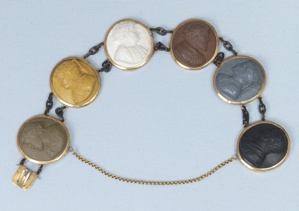 Six cameos of polished limestone joined in gold collets by paired brass chains, and having a small guard chain attached below the cameos at the clasp.  The subjects, in high relif, are profiles of Dante, Arioste, Tasso and three others not yet identified, probably also poets.
