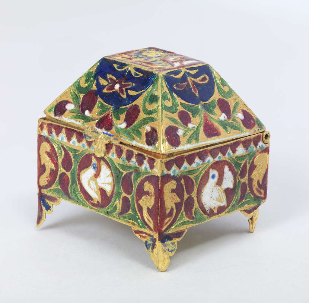 Rectangular, with four palmette bracket feet. Hinged cover with high canted sides and flat top. Gold, decorated in translucent red, green and blue, and opaque white champleve enamel. On cover, lion couchant and floral motifs. On sides small circular medallions with white fan-tail pigeons on red ground, and leaf motifs. On base, formal floral design.  It has an outer case or box with concave sides and domed cover, covered with garnet-colored silk embroidered in yellow, blue, black and cream, with small pieces of mirror applied. Lined with white crepe de Chine.