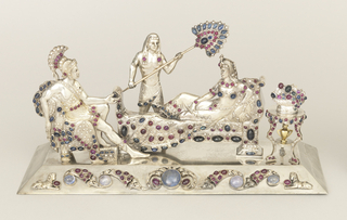 Cast silver, jewel encrusted tableau showing Roman soldier in full regalia seated opposite Egyptian woman reclining on couch, and fanned by standing servant; small tripod table to right of couch, holding bowl of fruit or flowers and urn on shelf below. All on rectangular plinth.