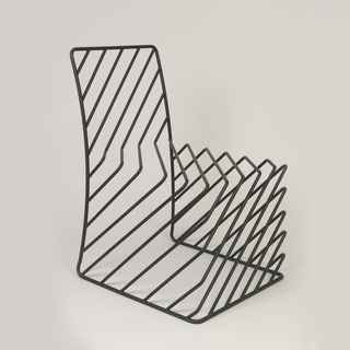 Side chair composed of black tubular steel rods, some diagonally set, bent to form the chair's outline and volume.
