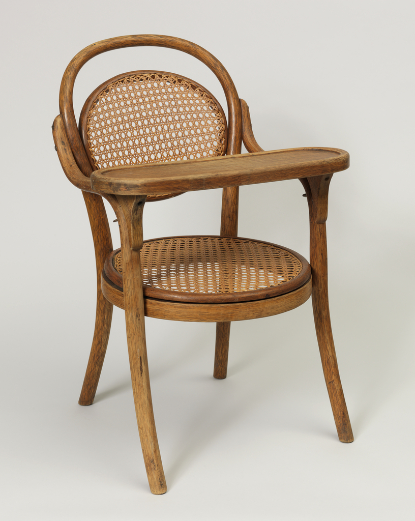 Frame of curving linear bent beechwood elements; caned, oval back joined to oval bent wood element comprising the back legs and back; caned circular seat secured between back and front legs; removable tray rests atop front legs