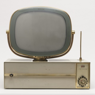 """Swiveling cathode ray television tube mounted on top of rectangular, white enameled metal case; top of case perforated; swiveling antenna mounted on rear right corner; front composed of perforated grill horizontally bisected by brass band and upright rectangular plastic panel on right with """"P"""" logo and """"Philco"""" above circular channel control knob."""