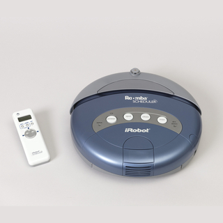 Circular form (a) of blue and gray plastic; control buttons in gray arched panel on top.