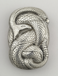 Oblong, with irregular curved sides conforming to shape of coiled rattlesnake, its mouth open, fangs displayed, fork-tongue extended, rattle at end of tail, overall raised scale texture to simulate snake skin, identical decoration on reverse. Lid hinged on side. Striker in recessed groove on bottom.