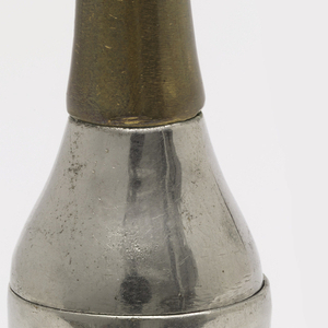 """In the form of a champagne bottle, the body silver color, the wrapped cork and neck brass , the label brass: inscribed """"Louis Roederere, Reims"""". Base of bottle neck (lid) hinged at back. Striker on bottle bottom."""