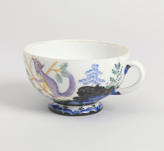 Rounded bowl on raised foot, loop handle; painted with squirrel amid stylized vegetation in polychrome enamel and silvering.