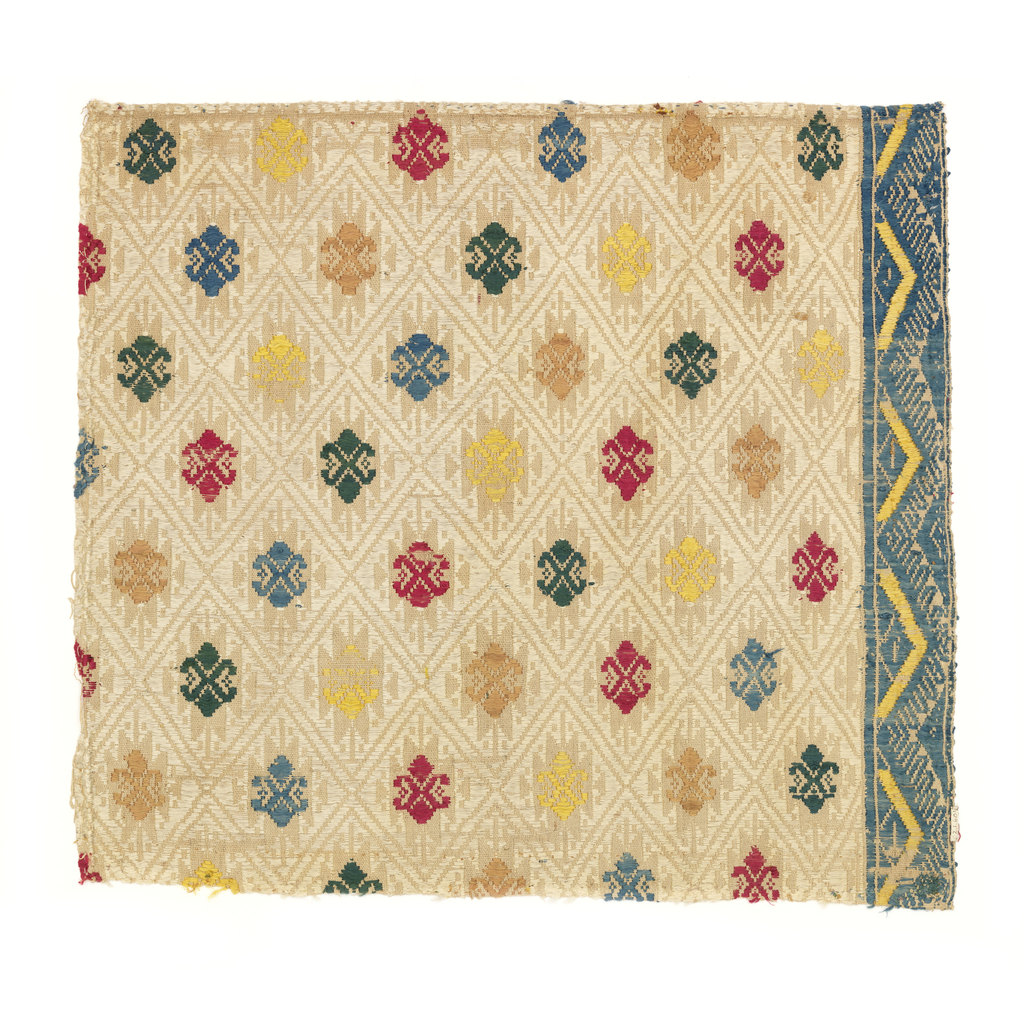 Textile fragment with a tone-on-tone diamond lattice pattern in the ground; each diamond is filled with a colored silk spot motif. In blue, green, yellow, red and pink silk on natural colored linen ground. Blue and yellow zigzag border on one side.