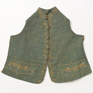 Waistcoat with standing collar and slightly curved hem, in green grosgrain silk embroidered with silk thread in a delicate pink and green floral design of tiny flowers sprinkled over the front. Denser sprays on pocket flaps, placket and standing collar. Originally made for a made and altered to fit a small boy.