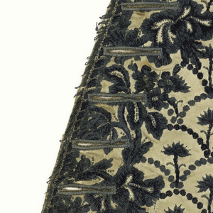 Waistcoat panel with dark blue chenille embroidery in a pattern of  imbricated scales, each containing a single floral sprig. Dense floral embroidery with French knots surrounds buttonholes.