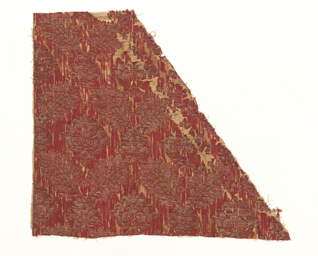 Woven silk with red ground and gold metallic pomegranate pattern. Badly abraded.