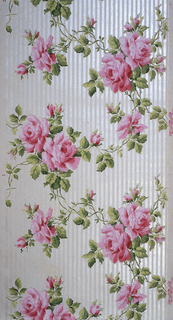 On striped white and gray ground, clusters of large pink roses and green leaves and vines.