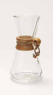 Small hourglass-shaped coffee maker of transparent glass with high neck and circular mouth molded with a narrow spout; tapered wood collar/hand grip at neck tied with leather thong with bead stop; small projecting dot as water level indicator in lower body, vertically aligned with spout.