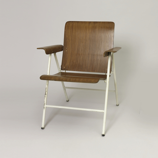 Folding chair, back and seat of contoured birch plywood sheets on steel frame, frame painted white; curved plywood arms.