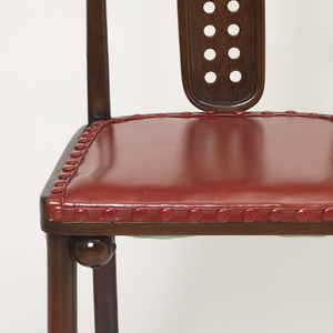 Rear legs and squared back frame consist of one piece of tapered, bent beechwood; back is slightly narrower at top than bottom; long, narrow, oval splat framed with bent beechwood and pierced with two columns of fifteen round holes each.  Cylindrical front legs. Legs reinforced at seat joint by two carved wooden spheres. Red leather upholstery on seat.  Leather-covered studs around perimeter of seat.