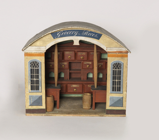 """Miniature of a store made with solid back and two sidewalls, front panels showing two painted windows and central opening for doorway with """"Grocery Stores"""" above it. Against the back wall, a cabinet with shelves and partitions and 16 drawers (-2b - -2l) each with a gold painted knob and handwritten paper label. One each for: almonds, annis seed, cacao, cinnamon, cloves, fenel, mace, millet, pepper, pimento, raisins, rice, saffron, sape, vermicelle (one drawer not labelled); two free-standing barrels (-2l and -2m), and two tables (-2n and -2o), each with a post (-2p and -2q) supporting one end of an arch (-2r) from which hangs a pair of scales (-2x - -2z). Pencil scribblings over outside of structure.Possibly English. In 1820's style, possibly early 19th century."""