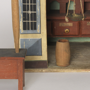 "Miniature of a store made with solid back and two sidewalls, front panels showing two painted windows and central opening for doorway with ""Grocery Stores"" above it. Against the back wall, a cabinet with shelves and partitions and 16 drawers (-2b - -2l) each with a gold painted knob and handwritten paper label. One each for: almonds, annis seed, cacao, cinnamon, cloves, fenel, mace, millet, pepper, pimento, raisins, rice, saffron, sape, vermicelle (one drawer not labelled); two free-standing barrels (-2l and -2m), and two tables (-2n and -2o), each with a post (-2p and -2q) supporting one end of an arch (-2r) from which hangs a pair of scales (-2x - -2z). Pencil scribblings over outside of structure.Possibly English. In 1820's style, possibly early 19th century."