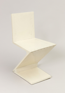 Z-form chair constructed of wide planks; rough construction painted white.