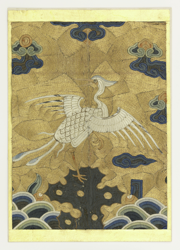 An egret, embroidered in white, is poised on a rock which is worked in dark blue against gold sky; cloud bands in colored silks above.