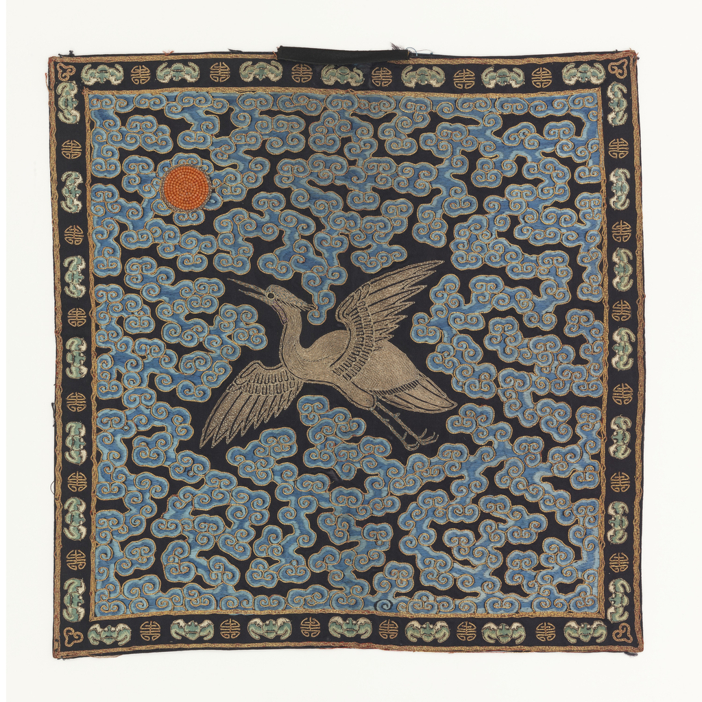 Rank badge for a civil official. Embroidered silk and metallic yarns showing a bird facing a sun disk, on a ground of clouds.