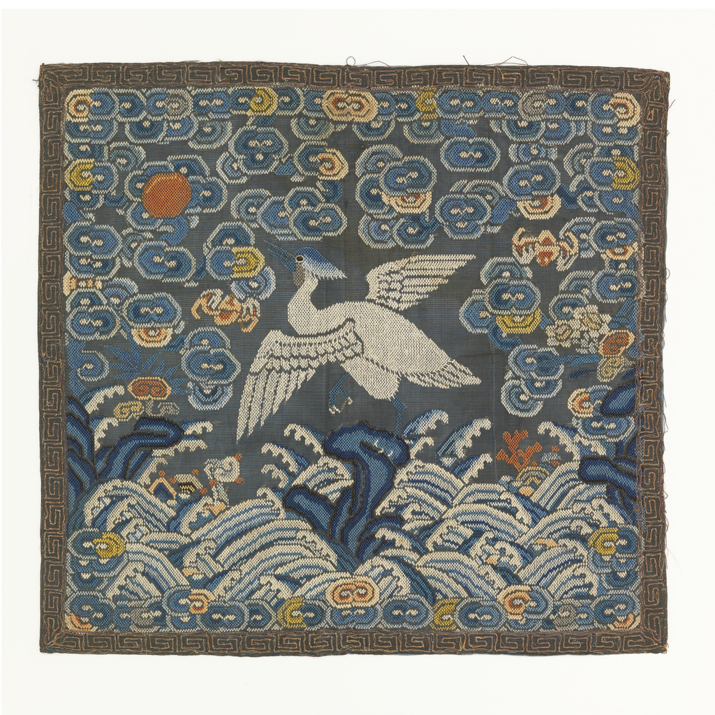 Rank badge for a civil official. Embroidered silk showing a bird facing a sun disk surrounded by auspicious symbols. Ground of clouds with diagonal lines at bottom and meandering key border. Lined with blue silk.