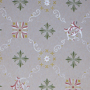 On gray ground, white scroll treillage with four motif variations: green foliate cross, yellow floral wreath, yellow and red leaf-tulip motif, and white and red scroll motif.