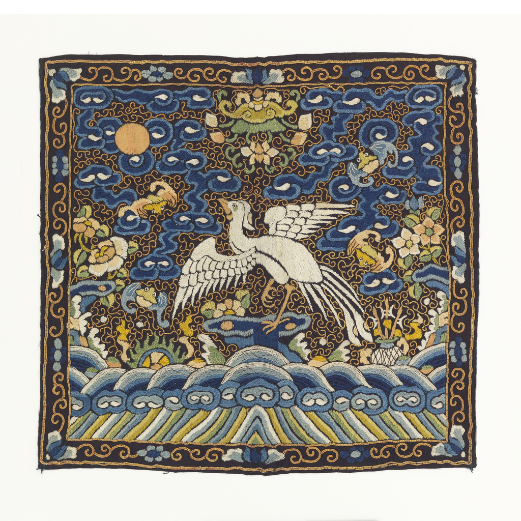 Rank badge for a civil official. Embroidered silk showing a bird facing a sun disk. Ground of clouds with diagonal lines at bottom and scroll border. Lined with blue silk.