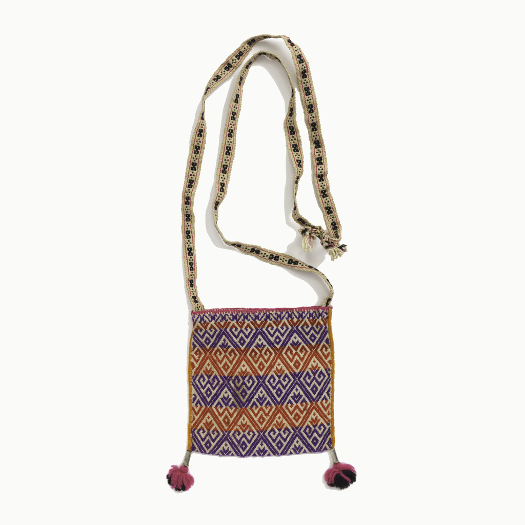 Small shoulder bag with geometrical designs and horizontal stripes in purple and red. On each bottom corner are tassels with metal tubes.