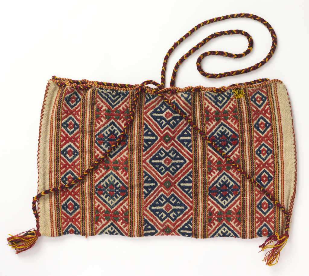 Rectangular wool bag patterned with stripes of geometric patterns in red and blue. Long tubular handle of braided yellow and red wool.