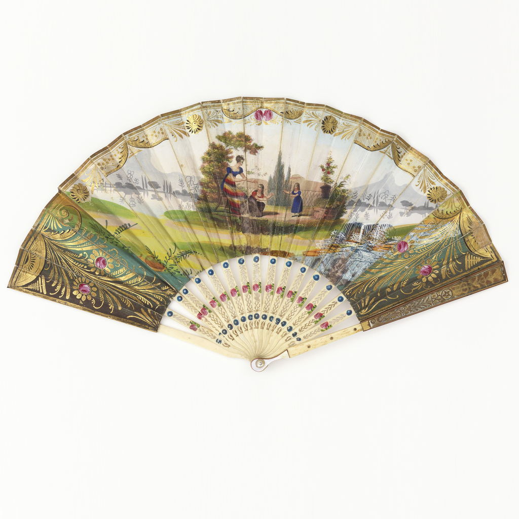 Fan leaf with  gilded and hand-painted lithograph scene of a woman and two girls in a landscape; verso: a family scene with a house and waterfalls. Ivory sticks gilded and pierced with seaweed motif.