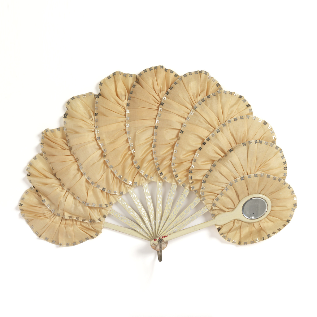 Brisé fan. White silk ruffle around each stick. Ribbon gathered and edges with sequins. Silvered wood sticks. One guard with oval mirror at end.