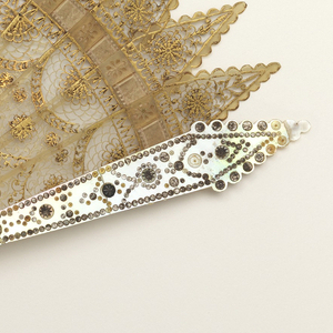 Brisé fan. Blonde horn sticks with scalloped ends, pierced in lace-like manner with designs of scallops, feathers and gilded rosettes. Mother-of-pearl guards decorated with steel piqués. Steel rivet. White silk connecting ribbon.