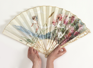 Pleated fan. Parchment leaf painted with thin gouache showing wind-blown cupid, aster flowers and cat-tails. Pierced mother-of-pearl sticks.
