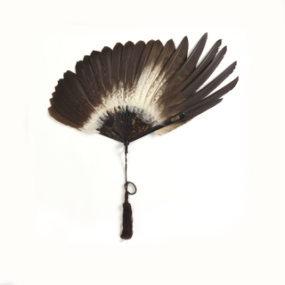 "Brisé fan. Twenty-two feathers of the golden eagle of the Scottish highlands mounted on tortoise shell sticks. One guard stick and a gold monogram: ""BF"" for Beatrix Farrand. Black silk ribbon and tassel."