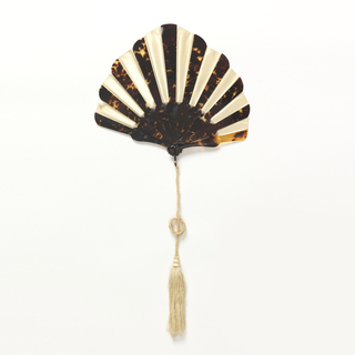 Pleated fan. White silk leaves glued between tortoise shell sticks of varying lengths. Black metal bail with cream-colored silk tassel.