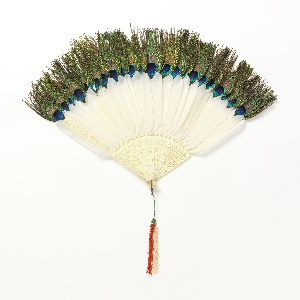 Brisé fan. Carved and pierced ivory sticks with peacock and peahen feathers. Gilt metal bail. Silk tassel.